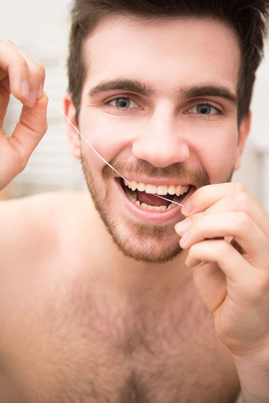 Using floss with toothpaste helps to clean up stains between teeth
